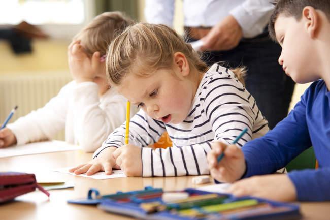 SchülerInnen und Schüler arbeiten an Arbeitsblättern im Klassenzimmer — Stockfoto