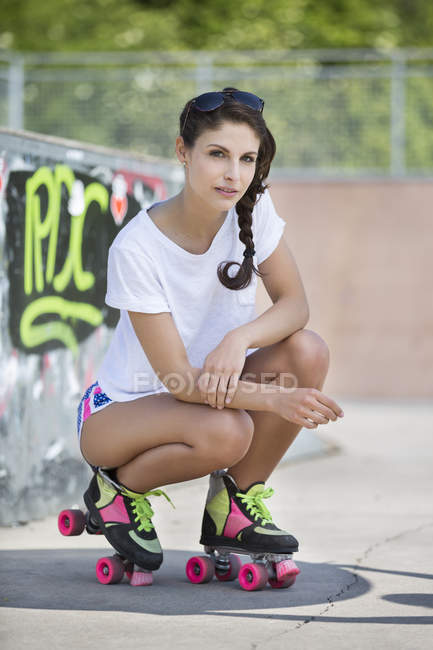 Female inline-skater crouching near ramp in skatepark — Stock Photo