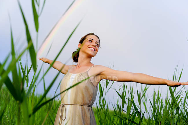 Happy young woman with outstretched arms standing between reed — Stock Photo