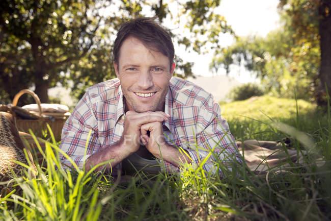 Усміхнений чоловік лежить на луг і дивлячись в камери — стокове фото