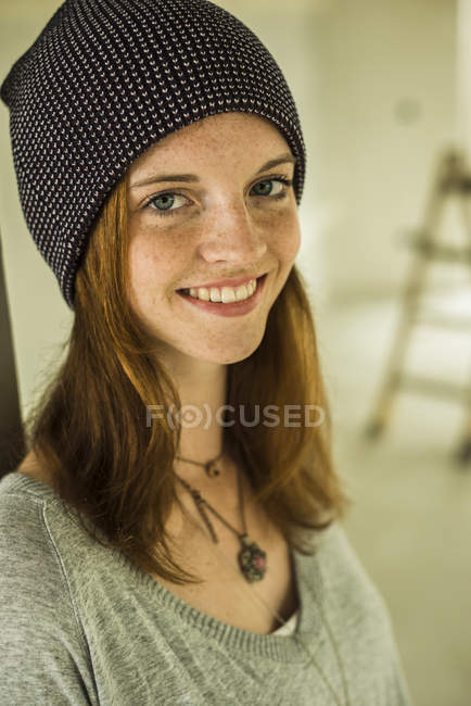 Portrait of smiling young woman wearing a cap — Stock Photo