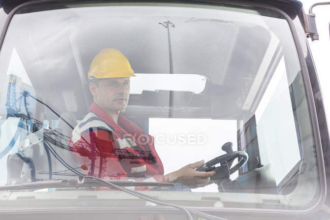 Man wearing safety vest in construction vehicle — Stock Photo