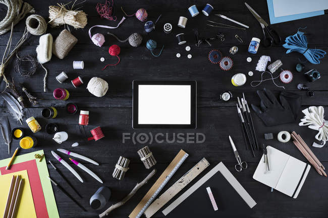 Arrangement of craft materials, tools  and digital tablet on black wood — Stock Photo