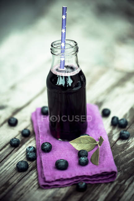 Bluberry juice in glass bottle, drinking straw — Stock Photo