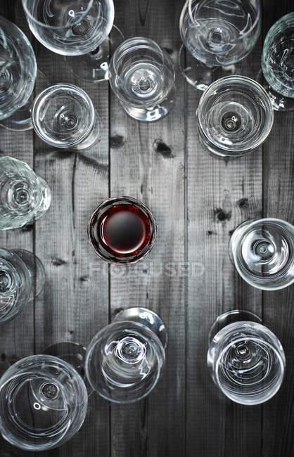 Copa de vino tinto y copas de vino vacías en madera - foto de stock