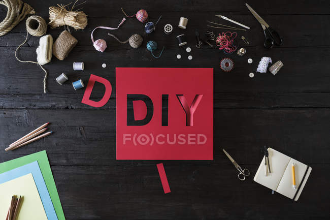 Craft materials and red cardboard with the word DIY on black wood — Stock Photo