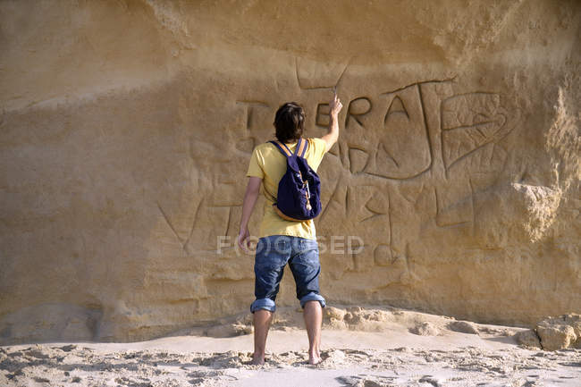 Man carving something on rock face — Stock Photo