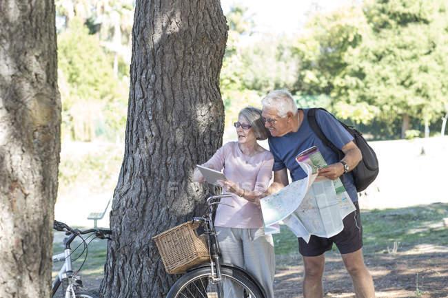 Старшая пара с велосипедами, глядя на цифровой планшет — стоковое фото