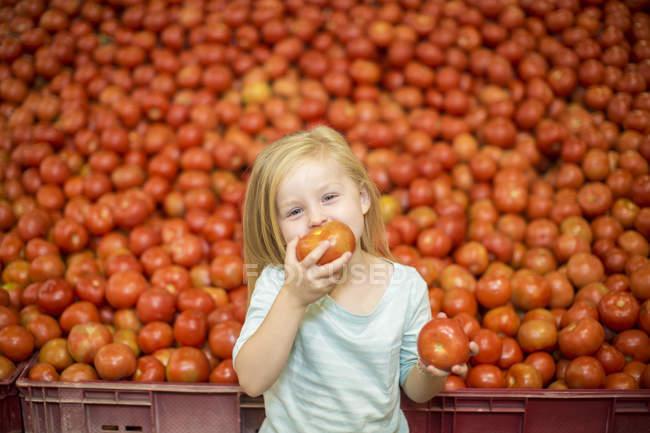 Kleines Mädchen vor dem Tomatenstand beim Tomatenessen — Stockfoto