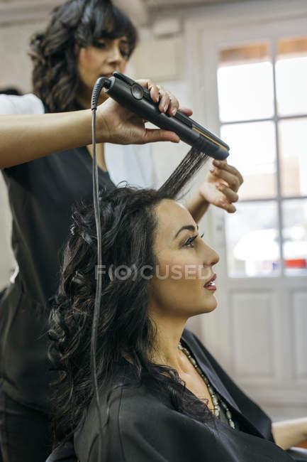 Parrucchiere femminile con ferro arricciacapelli sui capelli dei clienti — Foto stock