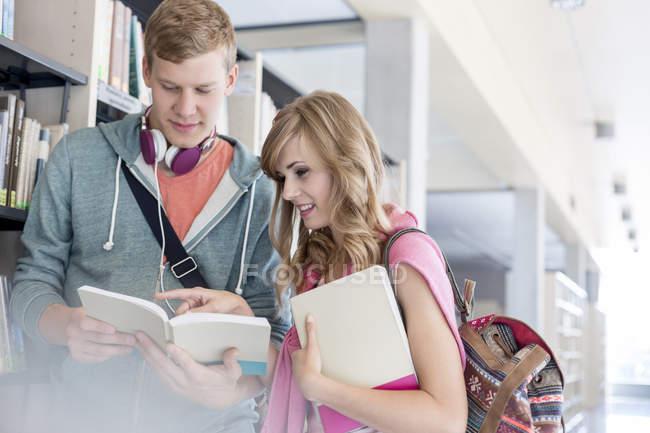 Deux étudiants, lecture de livre à la bibliothèque universitaire — Photo de stock