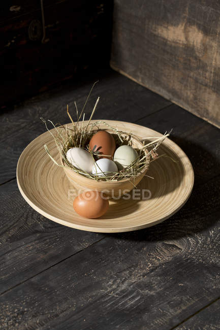 Easter nest with white and brown eggs in bowl on dark wood — Stock Photo