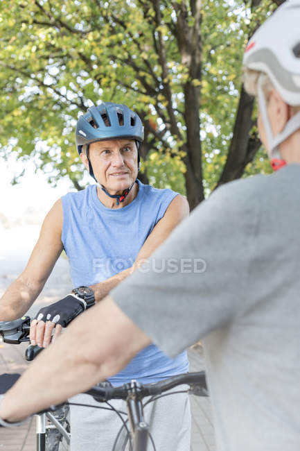 Portrait of senior man with cycling helmet and bicycles face to face with wife — Stock Photo