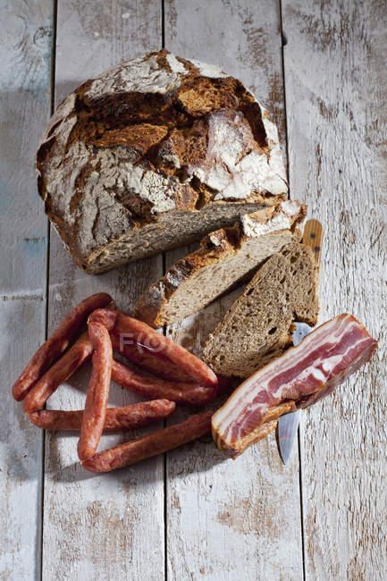 Pan y rebanadas de pan, tocino, salchichas y cuchillo - foto de stock