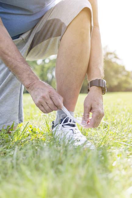 Sportive senior man tying his sneaker on a meadow — Stock Photo