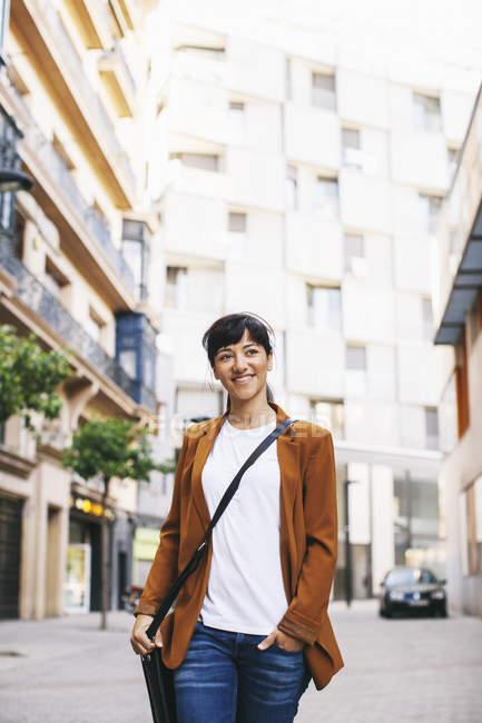 Lächelnde Geschäftsfrau, die auf einer Straße läuft — Stockfoto