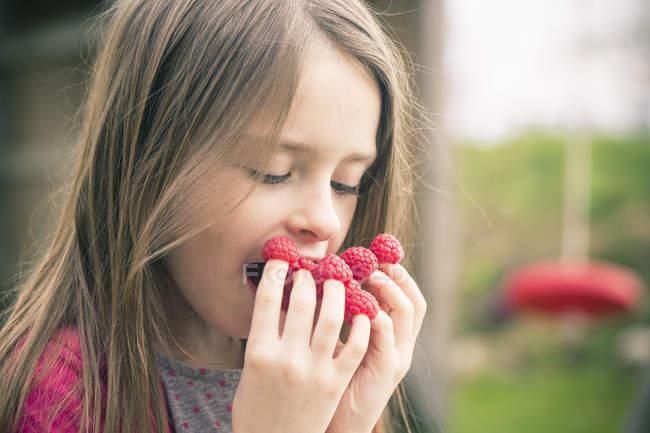 Девочка ест Малина от пальцев на открытом воздухе — стоковое фото