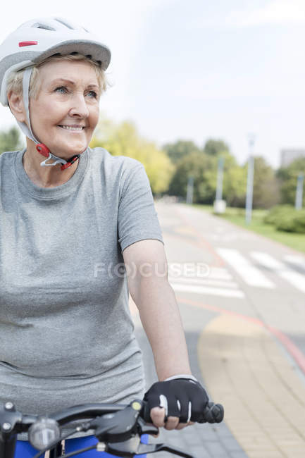 Portrait of smiling senior woman with cycling helmet on her bicycle — Stock Photo