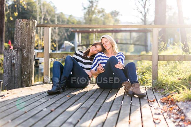 Лесбийская Пара, сидя на причал — стоковое фото