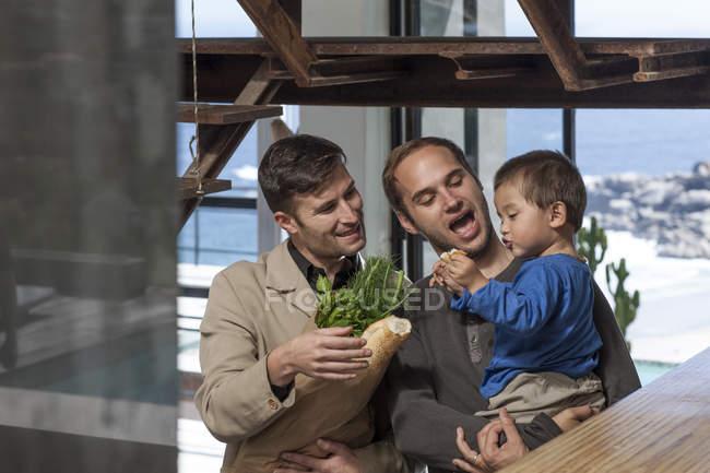 Гей-пара та дитина вдома з продовольчі товари — стокове фото