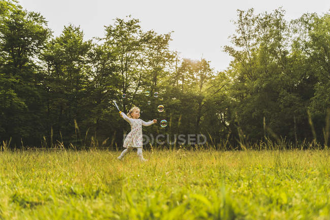 Girl on meadow surrounded by soap bubbles — Stock Photo