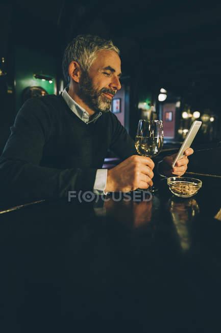 Sorrindo homem sentado no balcão de um pub usando smartphone — Fotografia de Stock