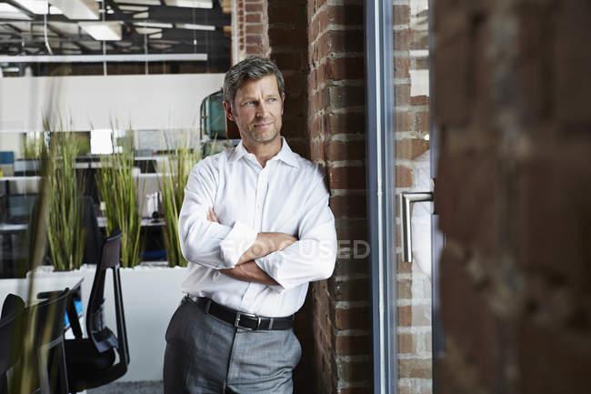 Uomo d'affari in ufficio che osserva dalla finestra — Foto stock