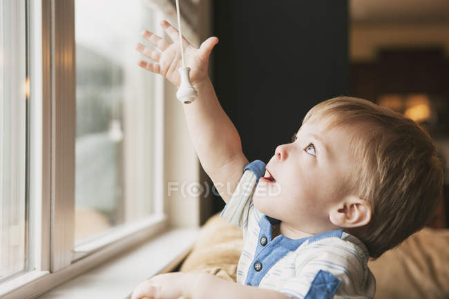 Toddler boy reaching out for window blind cord — Stock Photo