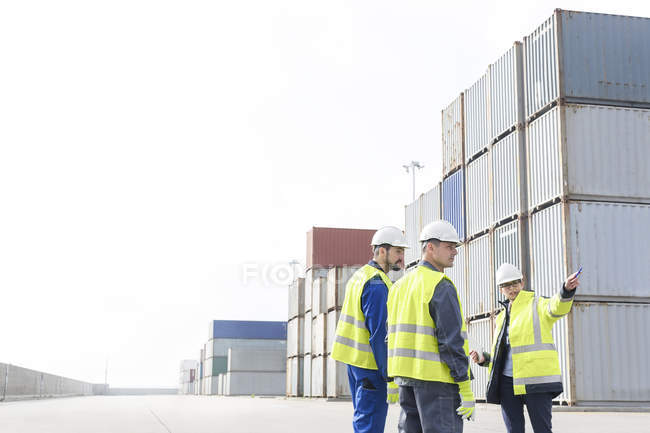 Woman and two men wearing protective clothing talking at container port — Stock Photo