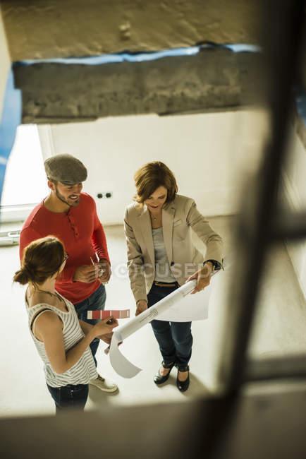 Plan d'architecte et jeune couple discutant la construction et l'échantillon de couleur — Photo de stock