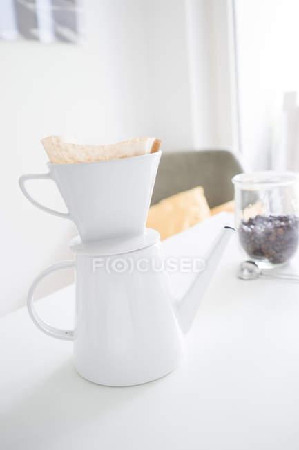 Filtro de café branco em pote de café em uma mesa — Fotografia de Stock