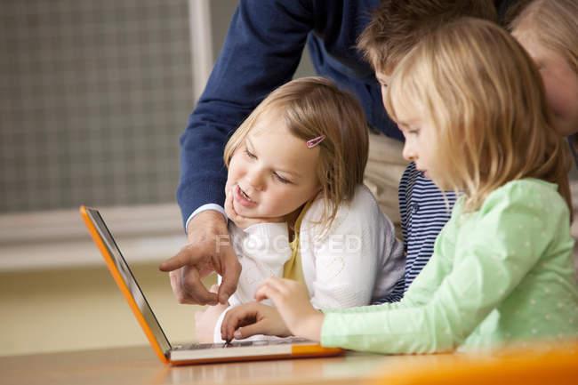 Insegnante con alunni che usano il computer portatile in classe — Foto stock