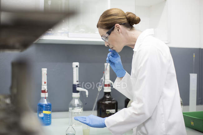 Female Scientist working in laboratory with pipettes — Stock Photo