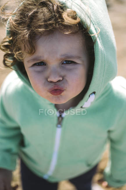 Portrait of pouting toddler girl in hooded jacket — Stock Photo