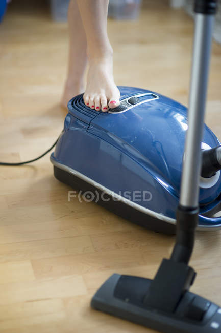 Woman's foot switching on vacuum cleaner — Stock Photo