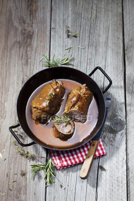 Involtini di manzo in brasatura pan, rosmary, asciugapiatti e coltello su legno — Foto stock