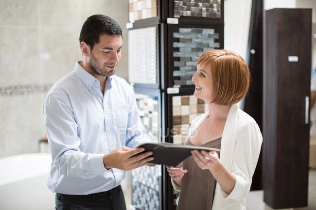 Bathroom shop salesman showing catalogue to female customer — Stock Photo