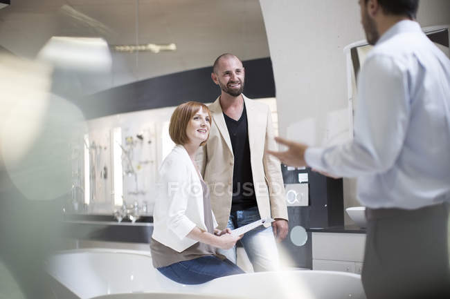 Bathroom shop salesman explaining customers some products — Stock Photo