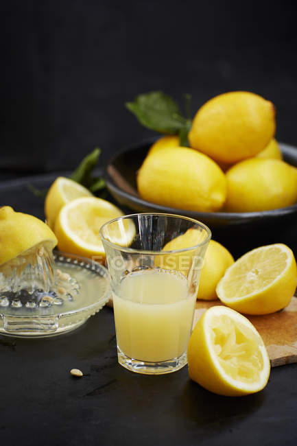 Sliced lemons in chopping board and freshly squeezed lemon juice — Stock Photo
