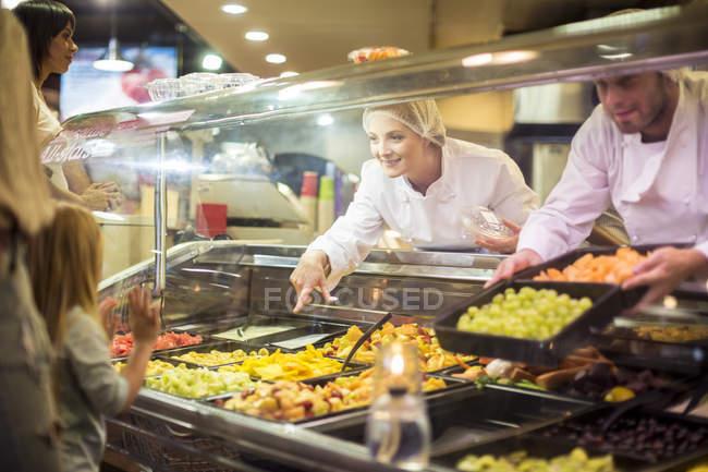 Customers choosing food from display at supermarket — Stock Photo