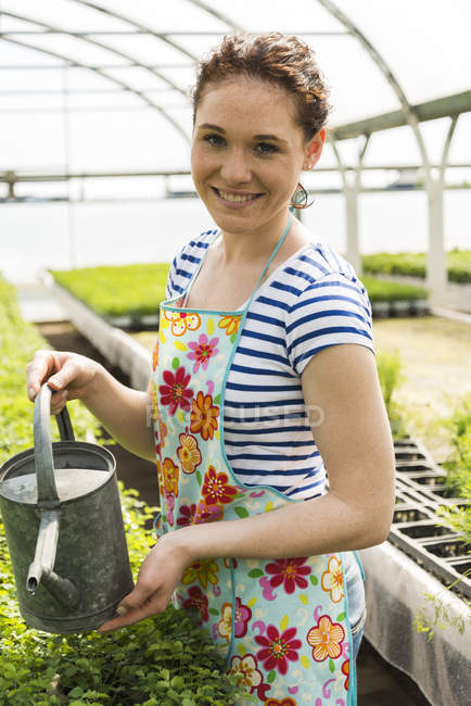 Young female gardener watering plants in plant nursery — Stock Photo