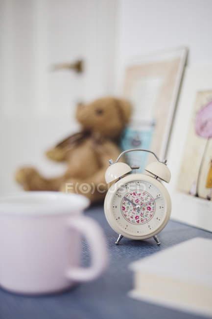 Reloj despertador de patrón floral en la mesa de noche en la habitación de la niña - foto de stock