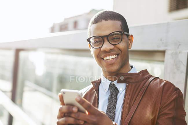 Hombre de negocios sonriente con teléfono inteligente - foto de stock