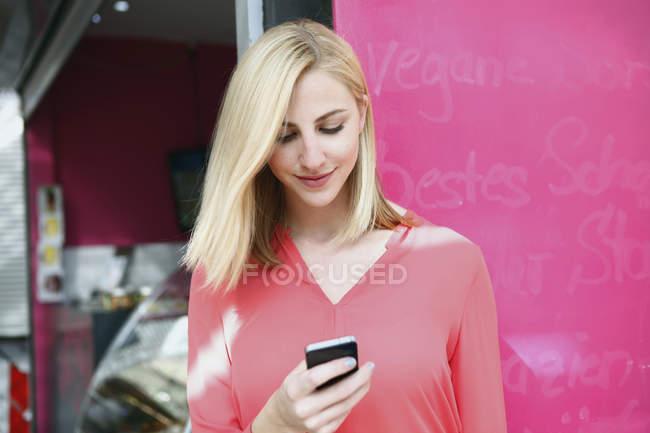 Lächelnde blonde Frau Blick auf ihr Smartphone vor einem Marktstand — Stockfoto