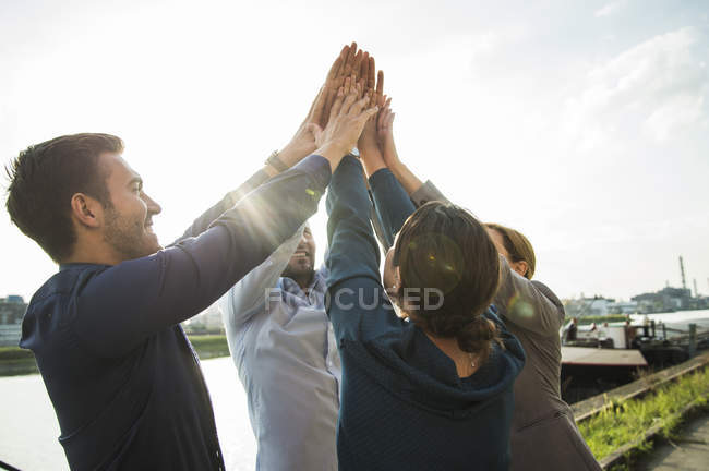 Four happy businesspeople raising their hands together — Stock Photo