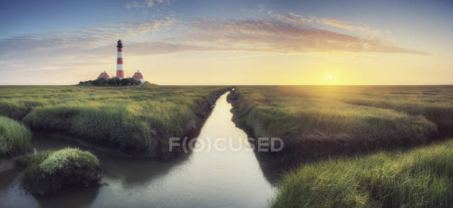 Lighthouse by the brook and coastal view — Stock Photo
