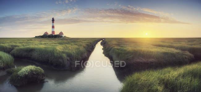 Маяк ручейком и прибрежным видом — стоковое фото