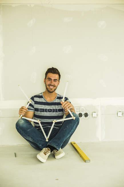 Lächelnder junger Mann sitzt an leerer Wand mit Taschenregel — Stockfoto