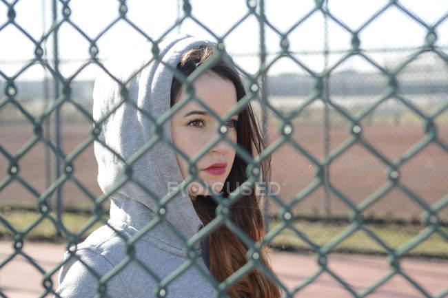 Портрет женщины в куртке с капюшоном за сеткой — стоковое фото