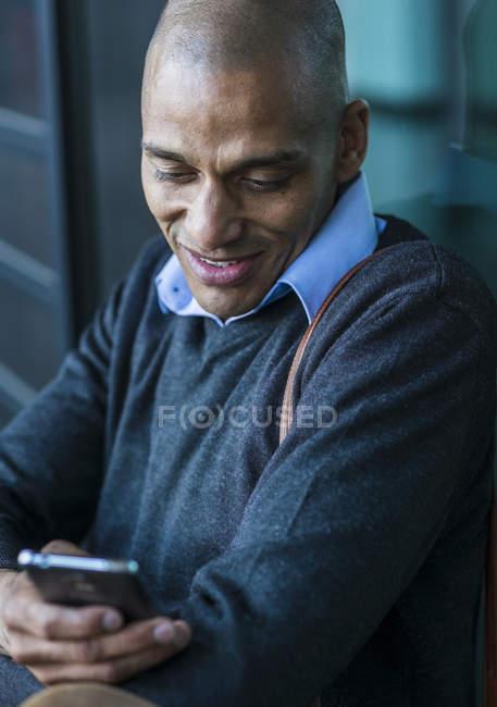 Улыбающийся мужчина на улице смотрит на смартфон — стоковое фото